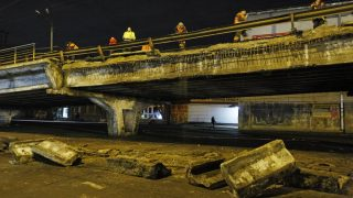 Employees of Emergency Situations Service attend a operation at the site of Shuliavsky bridge accident in Kiev, Ukraine, 27 February 2017. On Monday late evening parts of Shuliavsky bridge collapsed,and has damaged a car,as local media reported. (Photo by STR/NurPhoto)