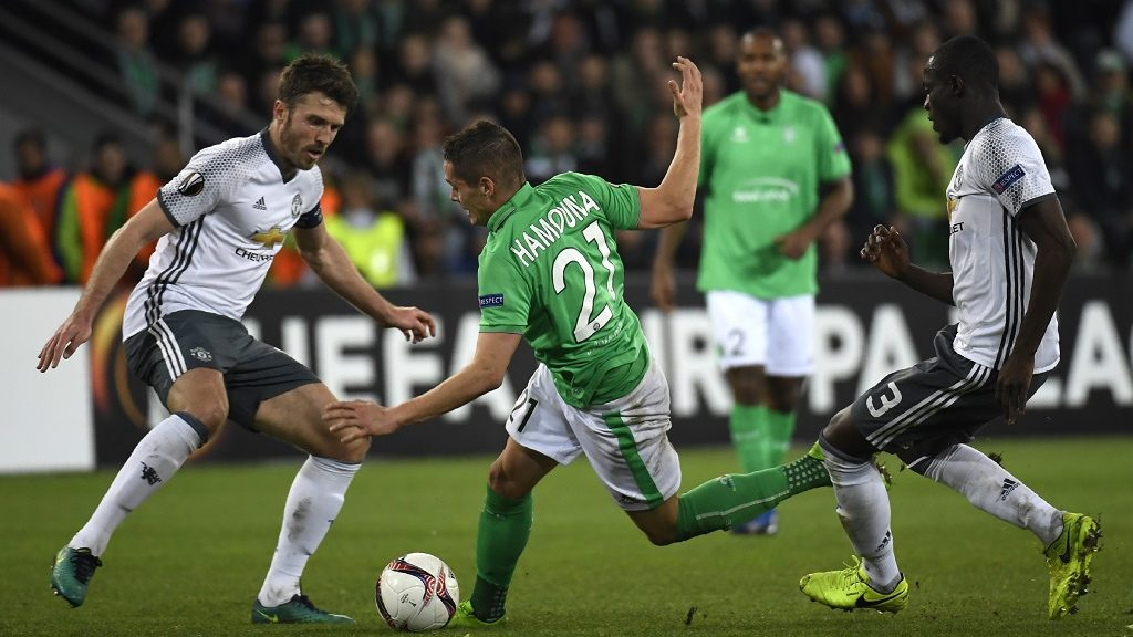 Saint-Etienne's French midfielder Romain Hamouma (C) vies with Manchester United's defender Michael Carrick (L) and defender Eric Bailly (R) during the UEFA Europa League football match between AS Saint-Etienne and Manchester United on February 22, 2017, at the Geoffroy Guichard stadium in Saint-Etienne, central France. / AFP PHOTO / PHILIPPE DESMAZES