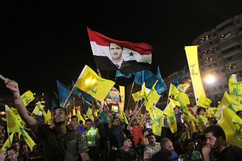 Lebanese Hezbollah supporters wave the movement's yellow flags and the Syrian flag decorated with an image of President Bashar al-Assad as they listen to a televised speech by Hezbollah chief Hassan Nasrallah to mark the sixth anniversary of the 2006 war with Israel in southern Beirut on July 18, 2012. AFP PHOTO/ANWAR AMRO / AFP PHOTO / ANWAR AMRO