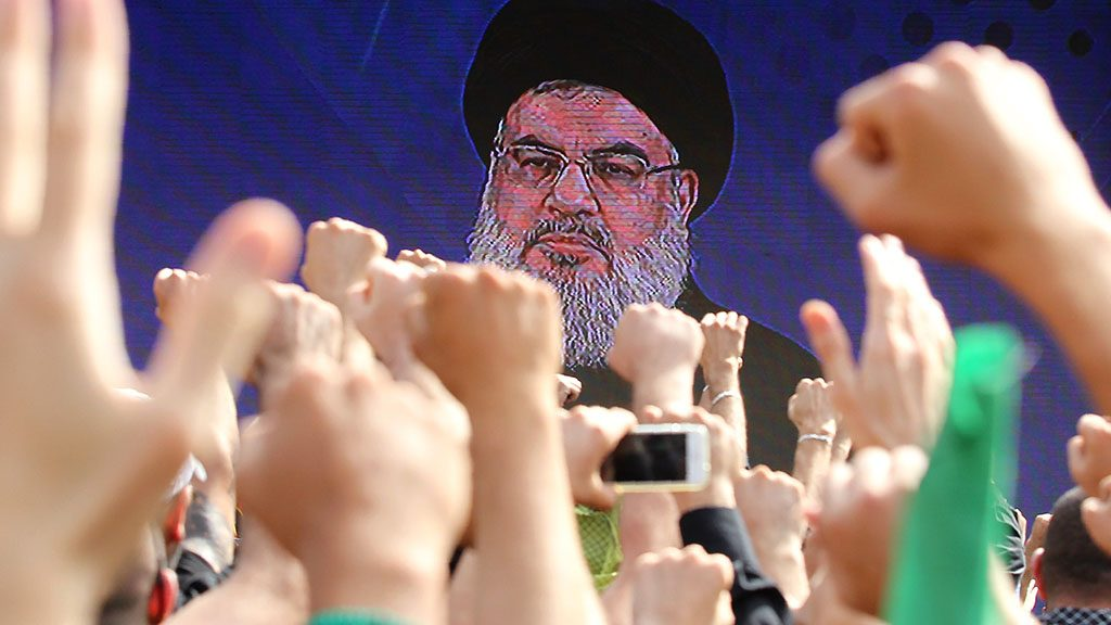 Hezbollah supporters hail their leader Hassan Nasrallah as he addresses a crowd during the commemoration of Ashura in a Beirut southern suburb on October 12, 2016.
