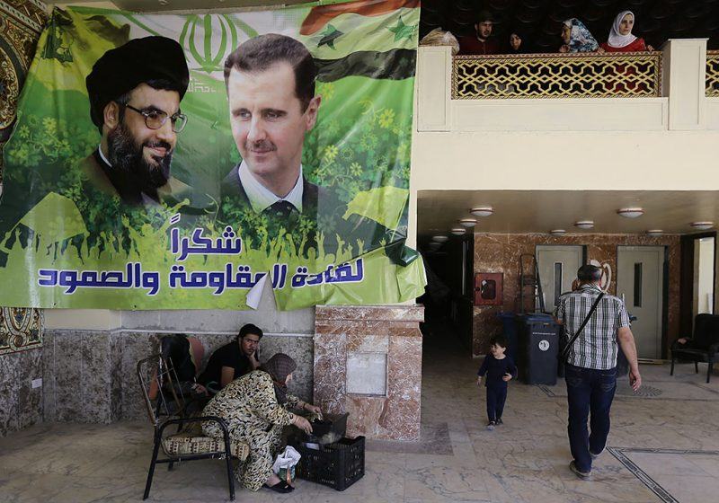Syrians gather in the lobby of a damaged apartment block, bearing a poster of Syrian President Bashar al-Assad (R) and Hassan Nasrallah, the chief of Lebanon's Shiite movement Hezbollah, following a car bomb near the revered Shiite shrine of Sayyida Zeinab, south of the Syrian capital Damascus on April 25, 2016.