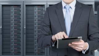 man with  tablet in front of server for data storage