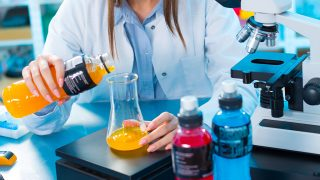 Quality control of food products. Young woman in chemical laboratory. Test of bottle portable drink