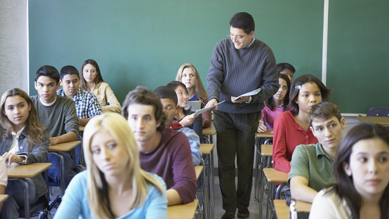 Male lecturer taking sheets of paper from students in a classroom