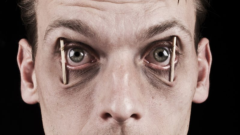 Man with sticks in his eyes trying to stay awake. Concept of workaholic or sleepless. Insomnia.