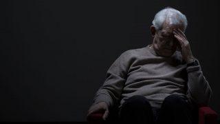 Despairing senior man on a dark background