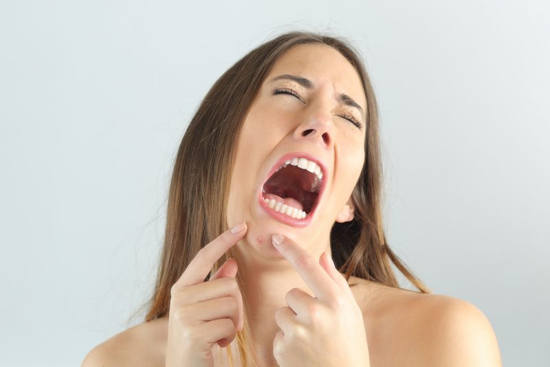Girl crying while pressing a pimple on her chin with a grey background