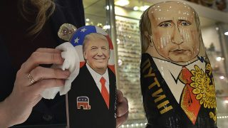 An employee polishes traditional Russian wooden nesting dolls, Matryoshka dolls, depicting US President-elect Donald Trump (L) and Russian President Vladimir Putin at a gift shop in central Moscow on January 16, 2017, four days ahead of Trump's inauguration. / AFP PHOTO / Alexander NEMENOV
