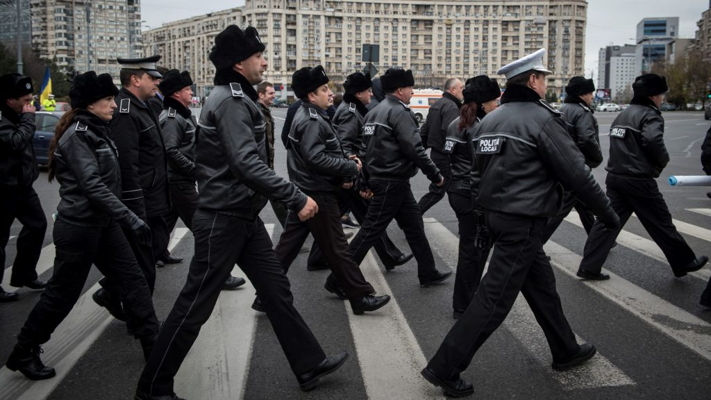 Romanian local police officers cross a boulevard during a protest in Bucharest on November 22, 2016. Around 1000 local police officers take part in a protest next to the Romanian Government headquarters to ask for the lower of the retirement age as the actual age is 65 years.  / AFP PHOTO / DANIEL MIHAILESCU