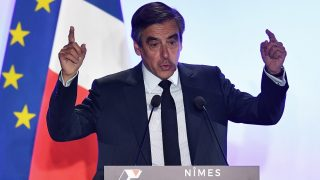 French presidential election candidate for the right-wing Les Republicains (LR) party Francois Fillon gestures while speaking during a campaign rally on March 2, 2017 in Nîmes, southern France. French police raided the Paris home of French right-wing candidate Francois Fillon on March 2 as part of a probe into allegedly fake parliamentary jobs given to his wife, several sources told AFP. / AFP PHOTO / PASCAL GUYOT
