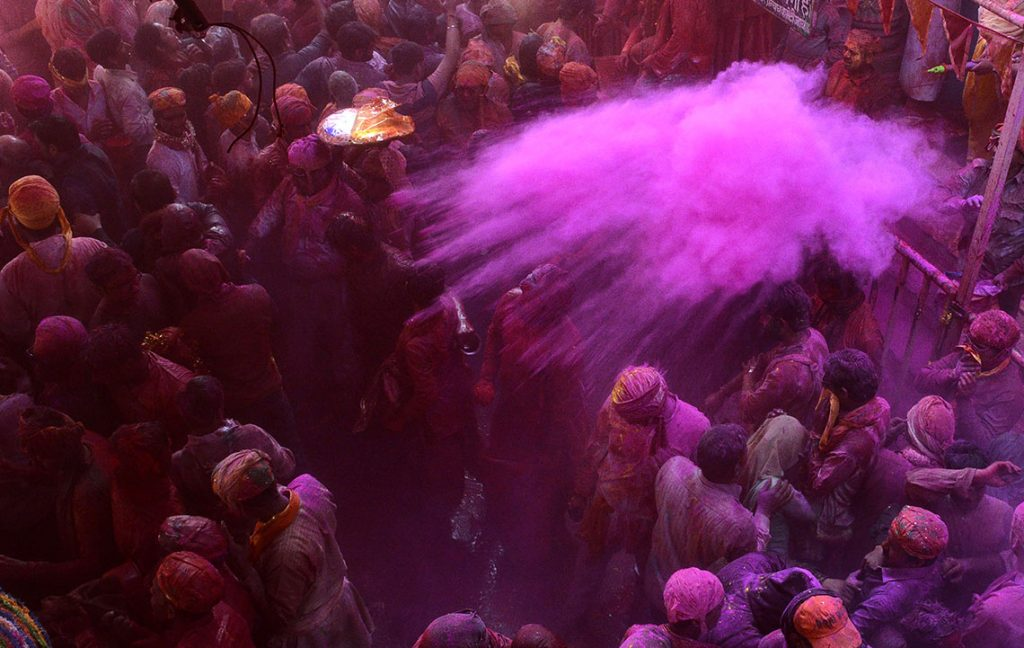 """In this photograph taken on March 6, 2017, Indian devotees throw coloured powder during celebrations for Lathmar Holi in Barsana on the outskirts of Mathura in the northern Indian state of Uttar Pradesh.Lathmar Holi is a local celebration of the Hindu festival of Holi, usually some days ahead of the actual festival - it translates as 'that Holi in which people hit with sticks"""".  / AFP PHOTO / STR"""
