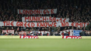 Bayern fans raise a banner to complain about the cost of match day tickets during the UEFA Champions League last 16 second leg football match between Arsenal and Bayern Munich at The Emirates Stadium in London on March 7, 2017. / AFP PHOTO / IKIMAGES / Ian KINGTON