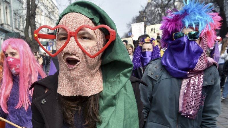 Costumed women shout slogans during a march as part of International Women's Day on March 8, 2017 in Kiev.  / AFP PHOTO / Sergei SUPINSKY