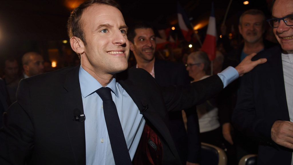 French presidential election candidate for the En Marche movement Emmanuel Macron greets supporters as he arrives for a campaign rally on March 9, 2017 in Talence, southwest France. / AFP PHOTO / Mehdi FEDOUACH