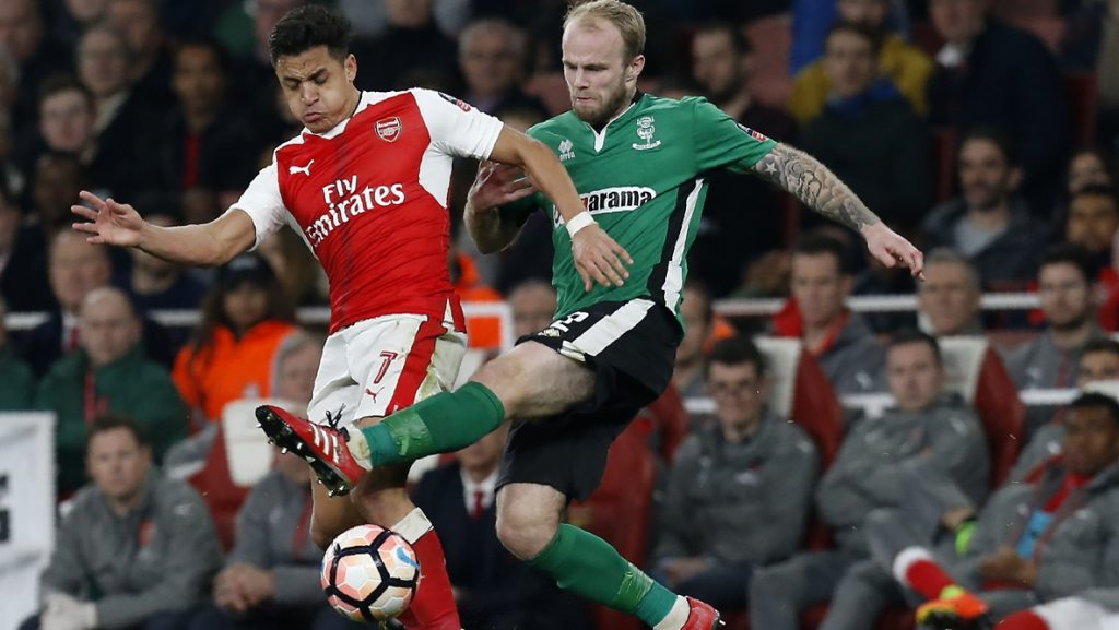 Arsenal's Chilean striker Alexis Sanchez (L) vies with Lincoln City's English defender Bradley Wood during the English FA cup quarter final football match between Arsenal and Lincoln City at The Emirates Stadium in London on March 11, 2017. Arsenal won the game 5-0. / AFP PHOTO / Ian KINGTON / RESTRICTED TO EDITORIAL USE. No use with unauthorized audio, video, data, fixture lists, club/league logos or 'live' services. Online in-match use limited to 75 images, no video emulation. No use in betting, games or single club/league/player publications.  /