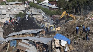 Excavators move earth as rescuers work at the site of a landslide at the main landfill of Addis Ababa on the outskirts of the city on March 12, 2017. At least 30 people died and dozens more were hurt in a giant landslide at Ethiopia's largest rubbish dump outside Addis Ababa, a tragedy squatters living there blamed on a biogas plant being built nearby. The landslide late on March 11 saw dozens of homes of people living in the dump levelled after a part of the largest pile of rubbish at the Koshe landfill collapsed, an AFP journalist said.  / AFP PHOTO / ZACHARIAS ABUBEKER