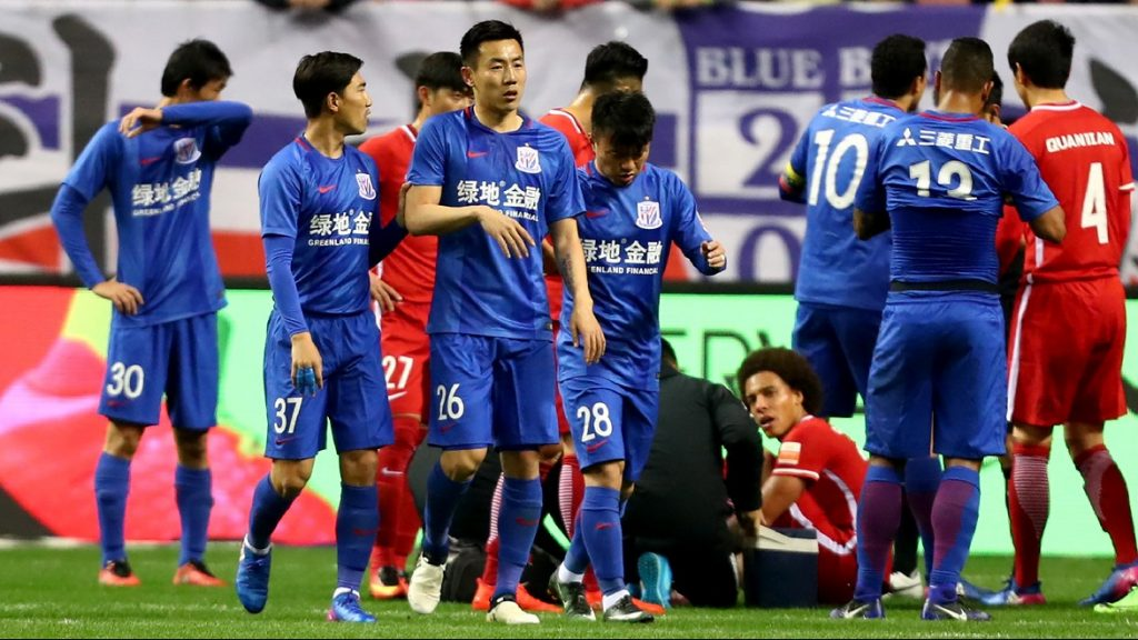 "This photo taken on March 11, 2017 shows Shanghai Shenhua's Qin Sheng (26) leaving the pitch after being given a red card during the Chinese Super League match against Tianjin Quanjian in Shanghai. Shanghai Shenhua will withhold the salary of China international Qin Sheng for the rest of the season after condemning the midfielder's ""abominable behaviour"" in stamping on Belgium's Axel Witsel at the weekend. / AFP PHOTO / STR / China OUT"