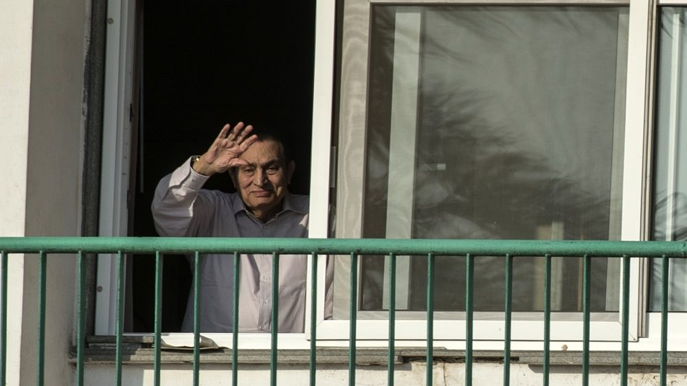 (FILES) This file photo taken on October 6, 2016 shows Egypt's former president Hosni Mubarak waving to people from his room at the Maadi military hospital in Cairo, as his supporters gather to celebrate the 43rd anniversary of October War victory. Egypt's ousted president Hosni Mubarak left a military hospital on March 24, 2017, where he had spent much of his six-year detention, his lawyer said. Mubarak had been cleared for release earlier this month after a top court finally acquitted him of involvement in protester deaths during the 2011 revolt that ousted him.  / AFP PHOTO / KHALED DESOUKI