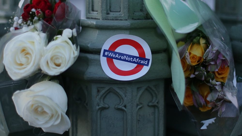 """Bunches of flowers and a sticker showing the London Underground logo and the words """"We are not afraid"""" in honour of the victims of the March 22 terror attack are pictured in central London on March 23, 2017.  Britain's parliament reopened on Thursday with a minute's silence in a gesture of defiance a day after an attacker sowed terror in the heart of Westminster, killing three people before being shot dead. Sombre-looking lawmakers in a packed House of Commons chamber bowed their heads and police officers also marked the silence standing outside the headquarters of London's Metropolitan Police nearby.  / AFP PHOTO / Daniel LEAL-OLIVAS"""