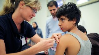 Physician Susanne Eipper vaccinates a refugee boy fromDamascus, Syria, against diseases such as mumps and measles at the Berlin State Office for Health and Social Affairs in Berlin,Germany, 01 October 2015. Around 2,000 refugees have been vaccinated inthe Berlin area since the refugees have started arriving in large groups. Photo: KAYNIETFELD/dpa