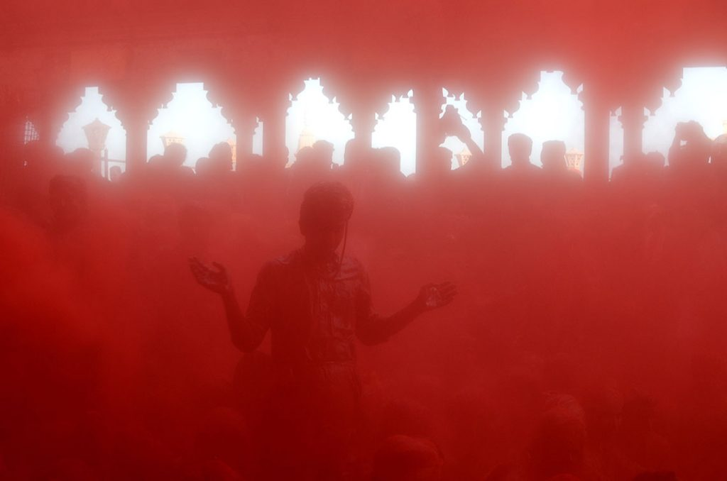 Indian reveler covered in coloured powder perform rituals inside a temple during the Lathmar Holi celebrations in the village of Barsana on March 6, 2017. holi, also called the Festival of Colours, is a popular Hindu spring festival observed in India at the end of the winter season on the last full moon day of the lunar month. (Photo by Ritesh Shukla/NurPhoto)