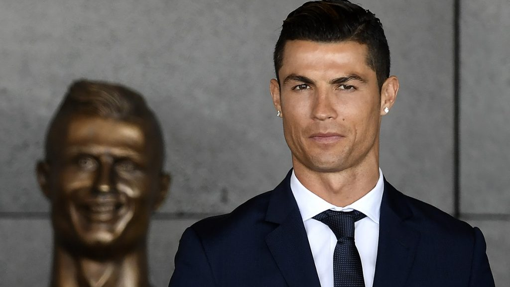 Portuguese footballer Cristiano Ronaldo stands past a bust presented during a ceremony where Madeira's airport in Funchal is to be renamed after Cristiano Ronaldo, on Madeira island, on March 29, 2017. Madeira airport, the birthplace of Portuguese footballer Cristiano Ronaldo, was renamed today in honor of the quadruple Ballon d'or and captain of the Portuguese team sacred European champion last summer. / AFP PHOTO / FRANCISCO LEONG