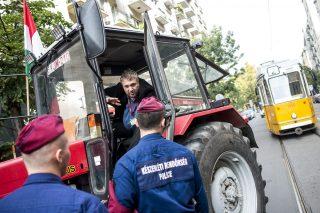 Budapest, 2015. október 5. Rendõrök igazoltatják Sallai R. Benedek LMP-s országgyûlési képviselõt, aki egy traktorral érkezik az Országház mélygarázsának bejárata elõtt tartott sajtótájékoztatójára a belvárosi Kossuth téren 2015. október 5-én. A helyszínen a párt aktivistái a földeladások ellen tiltakoztak. MTI Fotó: Marjai János