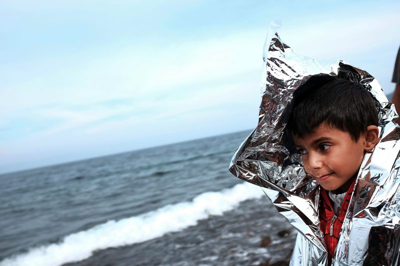 SIKAMINIAS, GREECE - OCTOBER 16:  A child is kept warm after arriving from Turkey on a raft onto the island of Lesbos on October 16, 2015 in Sikaminias, Greece. Dozens of rafts and boats are still making the journey daily as thousands flee conflict in Iraq, Syria, Afghanistan and other countries. More than 500,000 migrants have entered Europe so far this year. Of that number four-fifths of have paid to be smuggled by sea to Greece from Turkey, the main transit route into the EU. Nearly all of those entering Greece on a boat from Turkey are from the war zones of Syria, Iraq and Afghanistan.  (Photo by Spencer Platt/Getty Images)