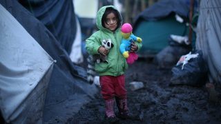 DUNKIRK, FRANCE - JANUARY 06: A young Kurdish girl holds her toys as she stands in the mud in a new migrant camp on January 6, 2016 in Dunkirk, France. Thousands of migrants continue to live in makeshift camps in the port towns of Calais and Dunkirk in northern France, where they try and board vehicles heading for ferries or through the tunnel in an attempt to reach Britain.  (Photo by Carl Court/Getty Images)