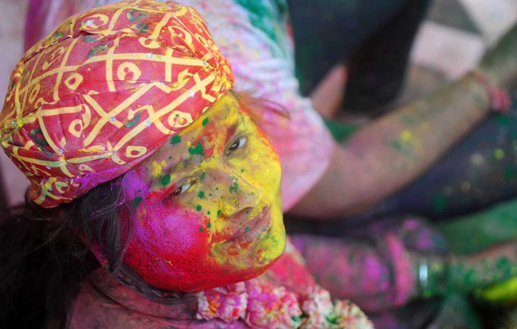 MATHURA, UTTAR PRADESH, INDIA - 2017/03/06: A devotee covered with a color powder reacts to camera during Lathmar Holi festival celebration at Radha Rani temple. (Photo by Prabhat Kumar Verma/Pacific Press/LightRocket via Getty Images)