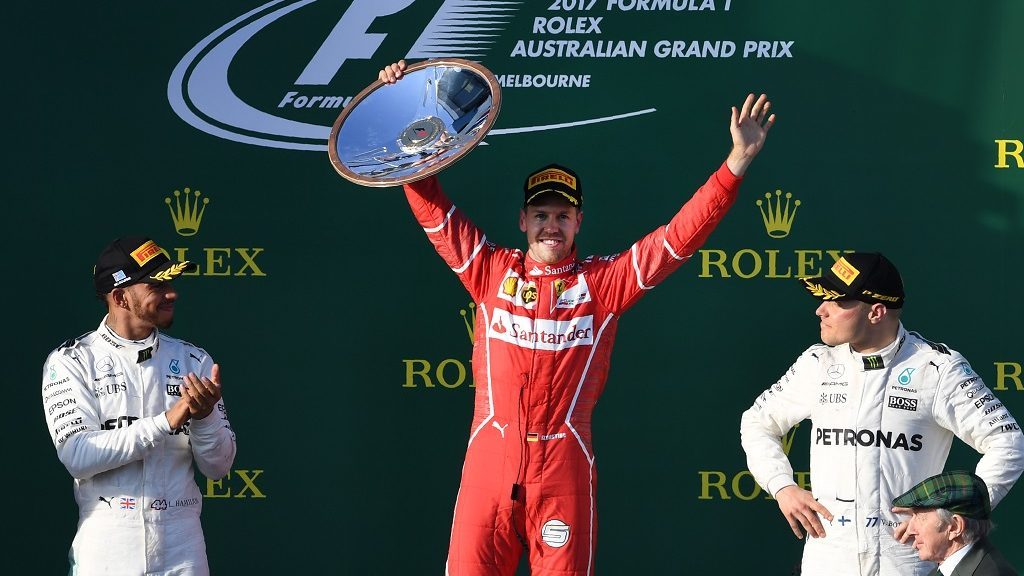 Ferrari's German driver Sebastian Vettel (C) celebrates on the podium with Mercedes' British driver Lewis Hamilton (L) and Mercedes' Finnish driver Valtteri Bottas (R) after winning the Formula One Australian Grand Prix in Melbourne on March 26, 2017.  / AFP PHOTO / WILLIAM WEST / -- IMAGE RESTRICTED TO EDITORIAL USE - STRICTLY NO COMMERCIAL USE --