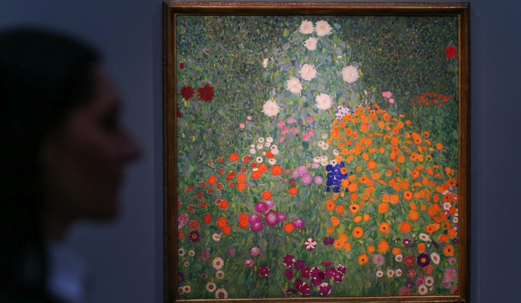 """(FILES) This file photo taken on February 22, 2017 shows an employee as she poses with an artwork by Austrian artist Gustav Klimt, entitled """"Bauerngarten, 1907"""", with an estimated price in excess of 35 million GBP (41 million EUR; 43 million USD), during a photocall ahead of the Impressionist & Modern, Surrealist and Contemporary Art sale at Sotheby's in London, on February 22, 2017. """"Bauerngarten, 1907"""", by Austrian artist Gustav Klimt, sold at auction on March 1, 2017, for 47.9 million GBP. / AFP PHOTO / Daniel LEAL-OLIVAS / RESTRICTED TO EDITORIAL USE - MANDATORY MENTION OF THE ARTIST UPON PUBLICATION - TO ILLUSTRATE THE EVENT AS SPECIFIED IN THE CAPTION"""