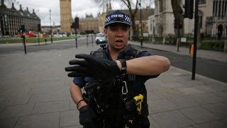 """An armed police officer gestures as he stands guard in Parliament Square, opposite the Houses of Parliament in central London on March 22, 2017 during an emergency incident.British police shot a suspected attacker outside the Houses of Parliament in London on Wednesday after an officer was stabbed in what police said was a """"terrorist"""" incident. / AFP PHOTO / DANIEL LEAL-OLIVAS"""