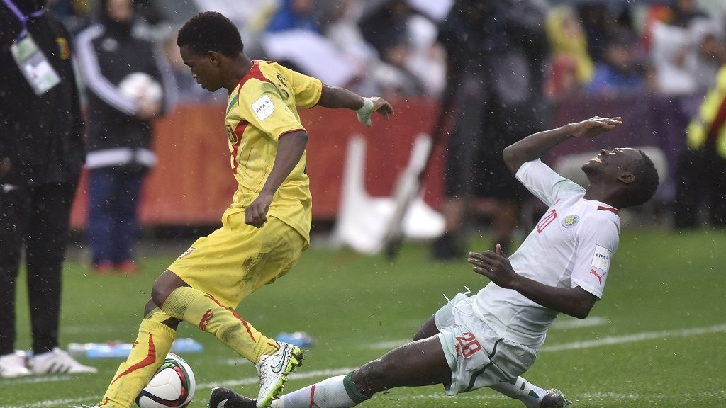 Souleymane Diarra (L) of Mali kicks out the ball as Remi Nassalan of Senegal goes down during the FIFA Under-20 World Cup football play-off for third place between Senegal and Mali at North Harbour Stadium in Auckland on June 20, 2015. AFP PHOTO / MARTY MELVILLE / AFP PHOTO / Marty Melville