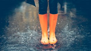 Close-up of woman in orange rubber boots jumping on the puddle