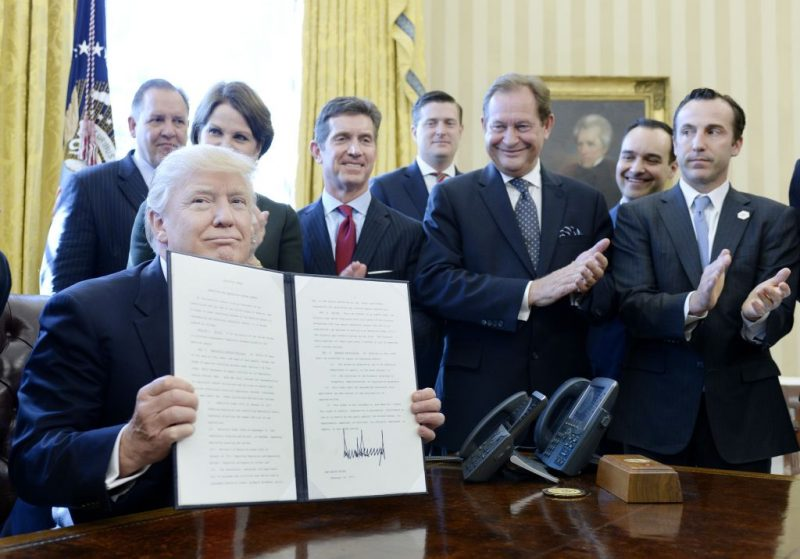 WASHINGTON, DC - FEBRUARY 24: (AFP OUT) U.S. President Donald Trump flanked by business leaders signs executive order establishing regulatory reform officers and task forces in US agencies in the Oval Office of the White House on February 24, 2017 in Washington, DC. Earlier in the day, Trump stated he would cut 75 percent of regulations. (Photo by Olivier Douliery - Pool/Getty Images)