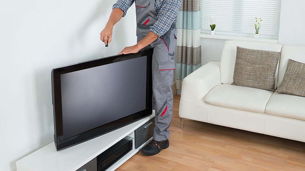Full length of male technician installing television at home