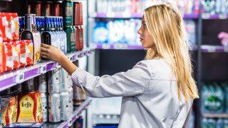 Woman in a supermarket. Liquors section. Paris, France VOISIN/PHANIE