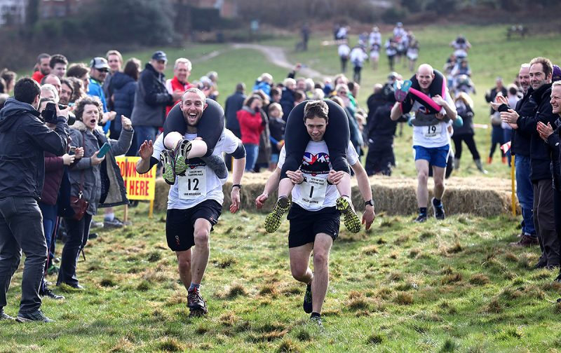 Competitors take part in the10th UK Wife Carrying Race in Dorking, Surrey. (Photo by Gareth Fuller/PA Images via Getty Images)