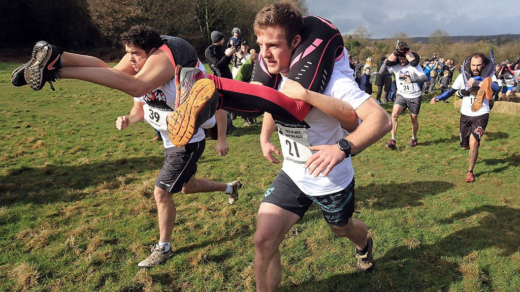 Jack Mckendrick from North Wales, carrying his partner Kirsty Jones (right) on his way to winning the 10th UK Wife Carrying Race in Dorking, Surrey. (Photo by Gareth Fuller/PA Images via Getty Images)