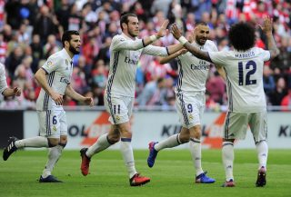 Real Madrid's players celebrate after French forward Karim Benzema (2R)scored their team's first goal during the Spanish league football match Athletic Club Bilbao vs Real Madrid CF at the San Mames stadium in Bilbao on March 18, 2017. / AFP PHOTO / ANDER GILLENEA