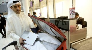 Kuwaiti social media activist Thamer al-Dakheel Bourashed puts his laptop inside his suitcase at Kuwait International Airport in Kuwait City before boarding a flight to the United States on March 23, 2017. Travellers across the Middle East have expressed frustration at a ban on large electronic devices for flights to the United States and Britain that has sparked confusion and speculation. From March 25, passengers on flights to the United States and Britain from major hubs in Turkey and the Arab world will have to check in any device larger than a smartphone, including laptops and tablets.   / AFP PHOTO / Yasser Al-Zayyat