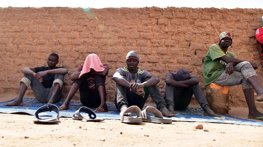"""Migrants from West Africa wait in a room at a """"ghetto"""" in Agadez, northern Niger, on April 1, 2017, as they wait to go to Libya from where they will attempt to reach Europe by crossing the Mediterranean sea. / AFP PHOTO / ISSOUF SANOGO"""