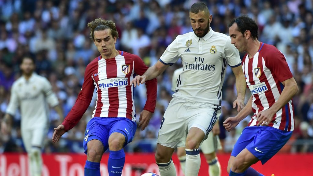Real Madrid's French forward Karim Benzema (C) vies with Atletico Madrid's French forward Antoine Griezmann (L) and Atletico Madrid's Uruguayan defender Diego Godin during the Spanish league football match Real Madrid CF vs Club Atletico de Madrid at the Santiago Bernabeu stadium in Madrid on April, 8, 2017. / AFP PHOTO / GERARD JULIEN
