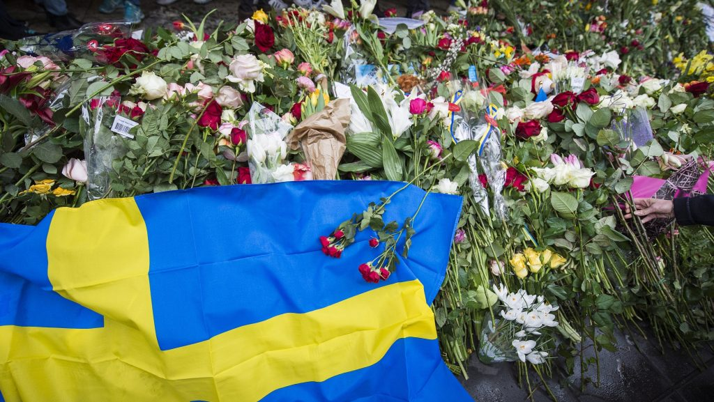 A woman lays flowers at a makeshift memorial to commemorate the victims of Friday's terror attack near the site where a truck drove into Ahlens department store in Stockholm, Sweden, on April 10, 2017.  Four people died and fifteen were injured when a truck plunged into a crowd at a busy pedestrian street in the Swedish capital on April 7, 2017. / AFP PHOTO / Jonathan NACKSTRAND