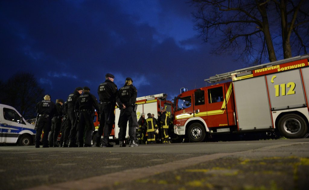 police and firefighhters are seen near the site wher Borussia Dortmund's bus was damaged by an explosion some 10km away from the stadium prior to the UEFA Champions League 1st leg quarter-final football match BVB Borussia Dortmund v Monaco in Dortmund, western Germany on April 11, 2017. / AFP PHOTO / Sascha Schuermann