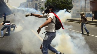 Demonstrators clash with the police during a rally against Venezuelan President Nicolas Maduro, in Caracas on April 19, 2017. Venezuela braced for rival demonstrations Wednesday for and against President Nicolas Maduro, whose push to tighten his grip on power has triggered waves of deadly unrest that have escalated the country's political and economic crisis. / AFP PHOTO / Ronaldo SCHEMIDT