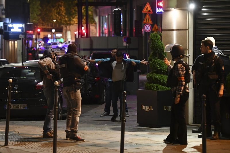 Police officers control men near the site of a shooting at the Champs Elysees in Paris on April 20, 2017. French anti-terror prosecutors said they opened a probe today into the shooting on Paris's Champs Elysees that killed one police officer and wounded two others. France's interior ministry said the attacker was killed after opening fire on police in the early evening on the world-famous boulevard.  / AFP PHOTO / FRANCK FIFE