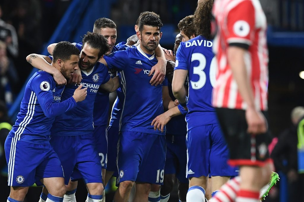 Chelsea's Brazilian-born Spanish striker Diego Costa (C) celebrates with teammates after scoring their third goal during the English Premier League football match between Chelsea and Southampton at Stamford Bridge in London on April 25, 2017. Chelsea won the game 4-2. / AFP PHOTO / Justin TALLIS / RESTRICTED TO EDITORIAL USE. No use with unauthorized audio, video, data, fixture lists, club/league logos or 'live' services. Online in-match use limited to 75 images, no video emulation. No use in betting, games or single club/league/player publications.  /