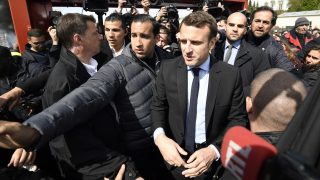 French presidential election candidate for the En Marche ! movement Emmanuel Macron arrives outside Whirlpool factory outside the Amiens Cathedral on April 26, 2017. Macron announced that he would meet with employees of the under-threat Whirlpool factory in Amiens after French far-right presidential candidate Marine Le Pen upstaged him by making a surprise visit to the factory as he was meeting workers' representatives without actually visiting the site. / AFP PHOTO / POOL / Eric FEFERBERG